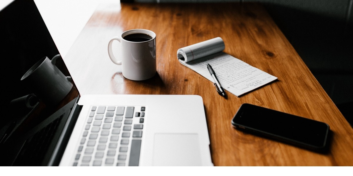 The why of business blogging: a table with a laptop, coffee mug, notebook and phoen