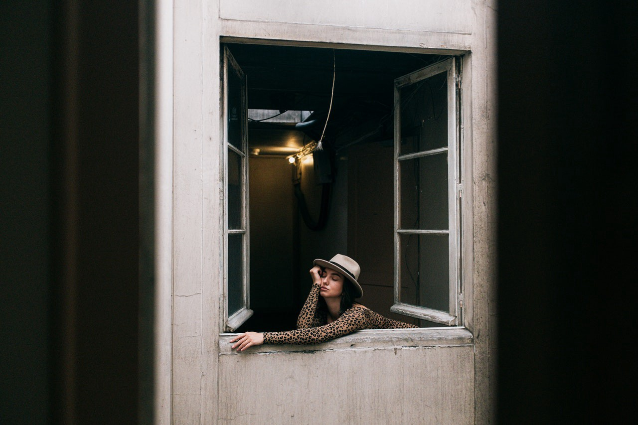 a woman sitting bored on a window