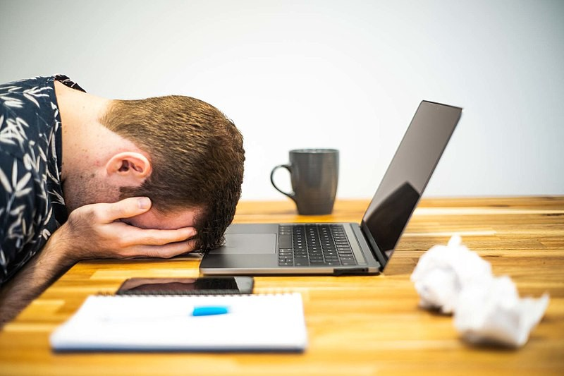 Stressed man with head on desk frustrated with work