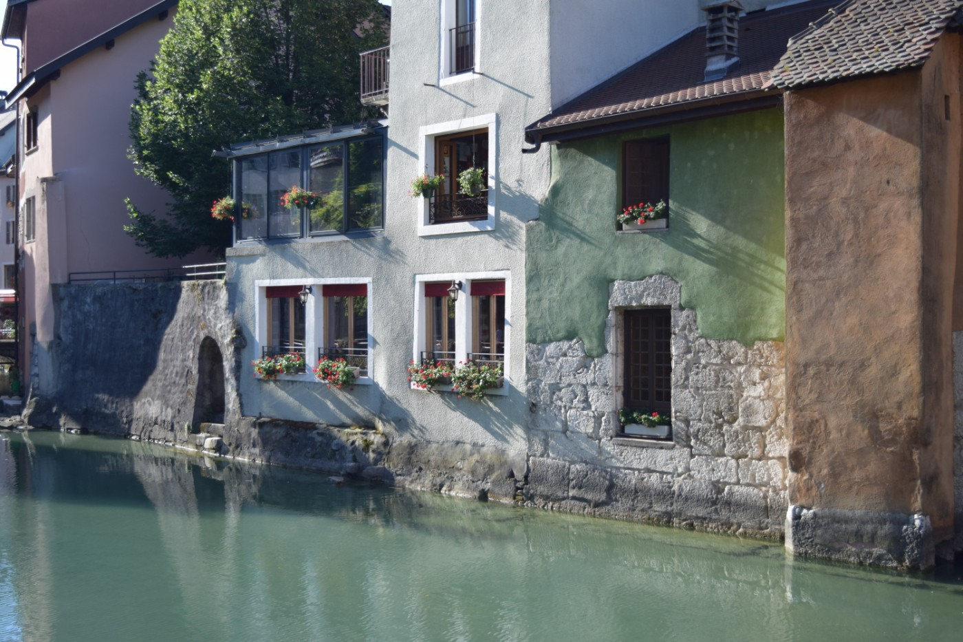 A green building and an orange building next to the canal that runs through Annecy's old town.