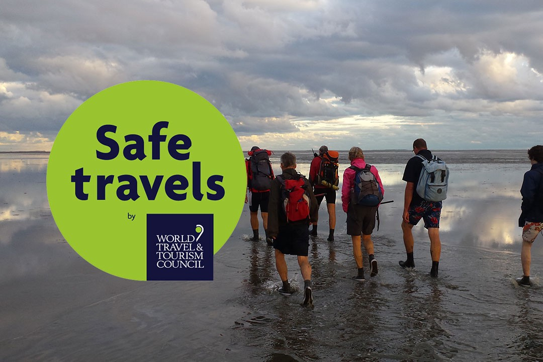 Safe Travels logo with group of tourists hiking along a beach