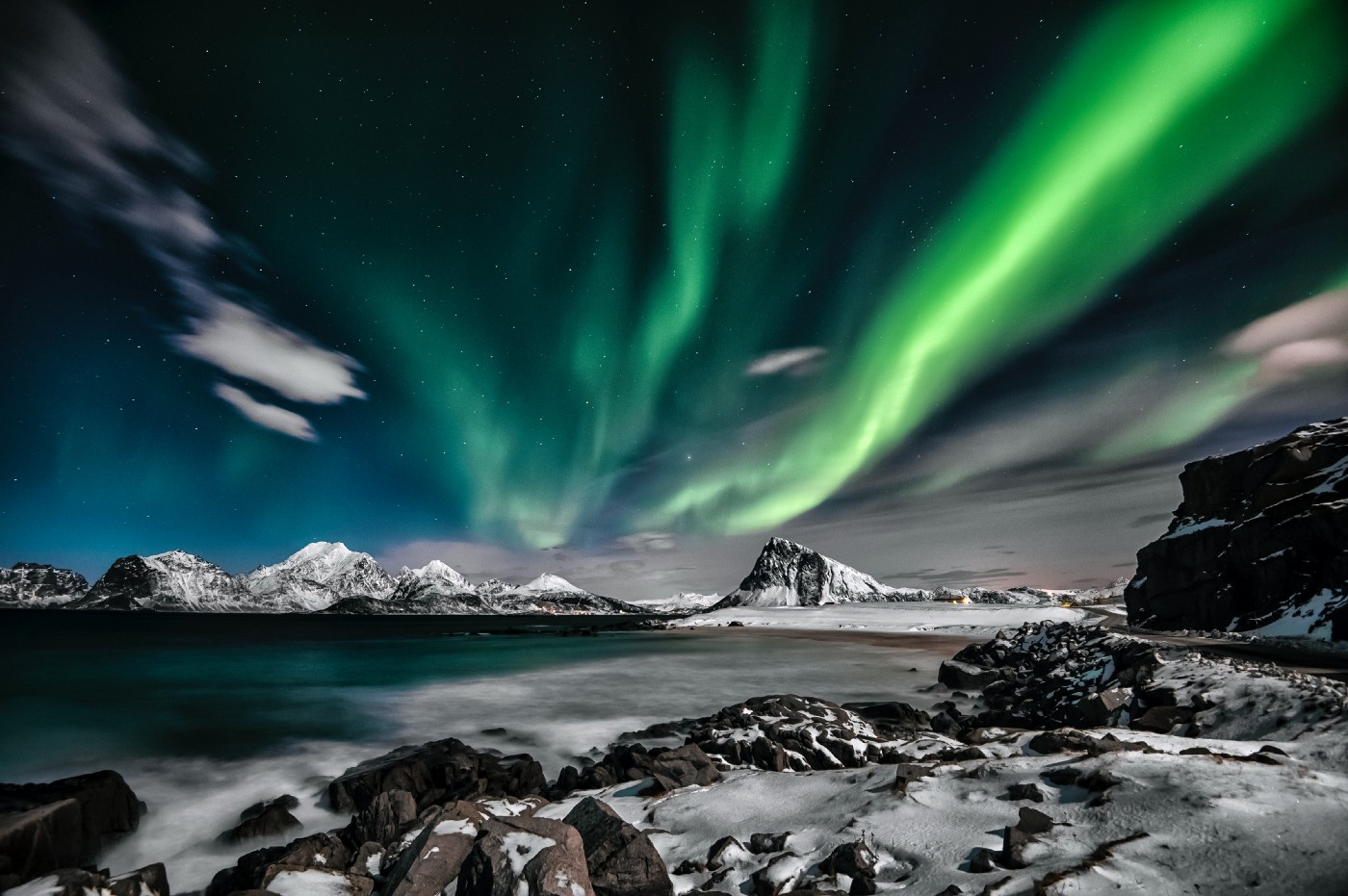 The Northern Lights with a body of water and mountains in the background