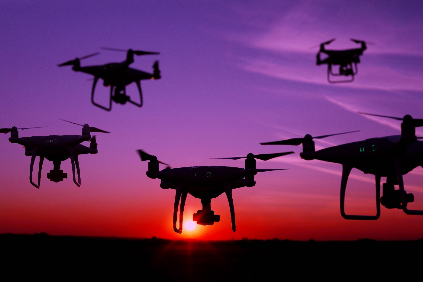 Five drone silhouettes in the sky at sunset