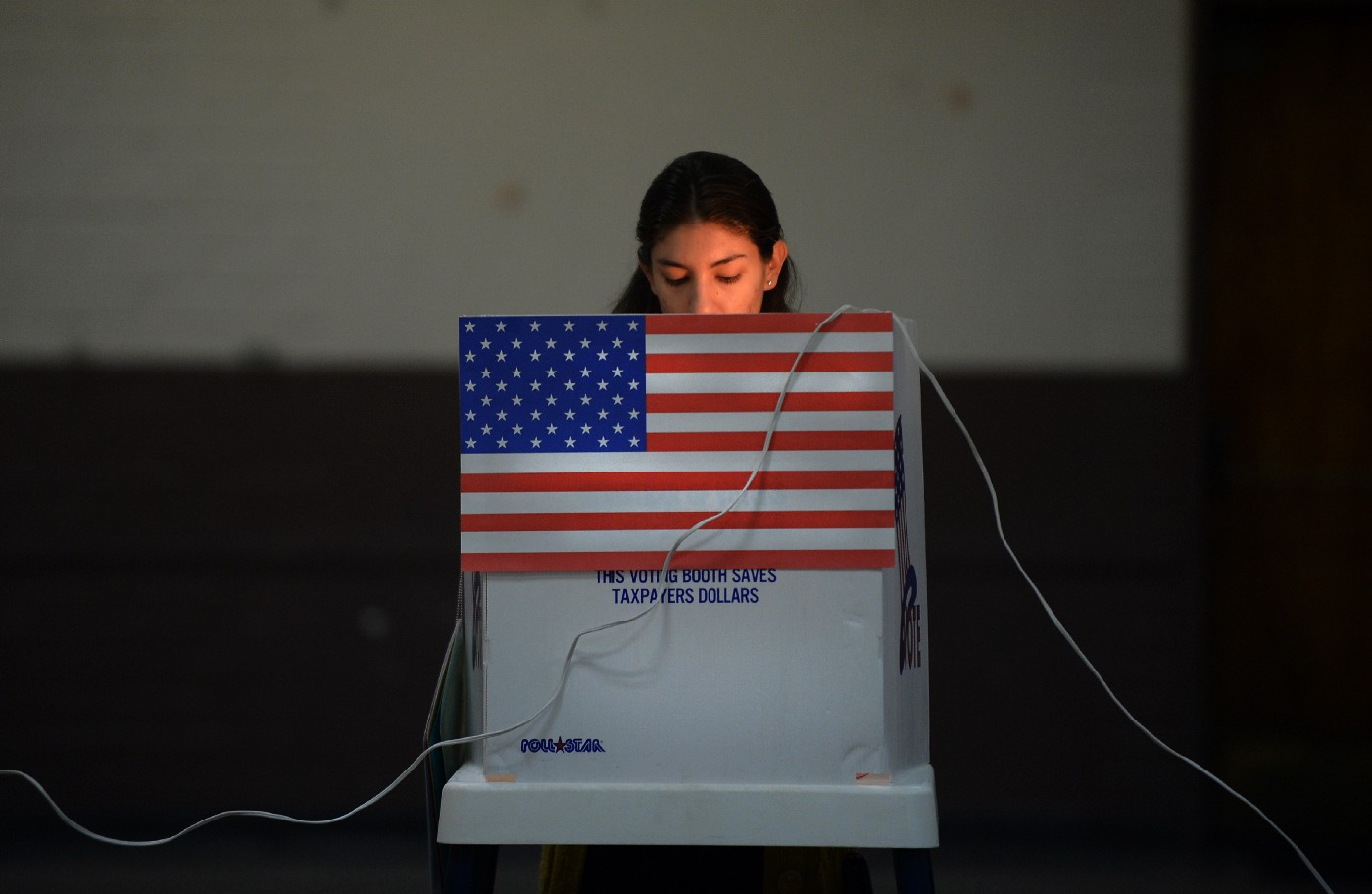 Latina woman voting at a poll in California. The booth has an American flag on it.
