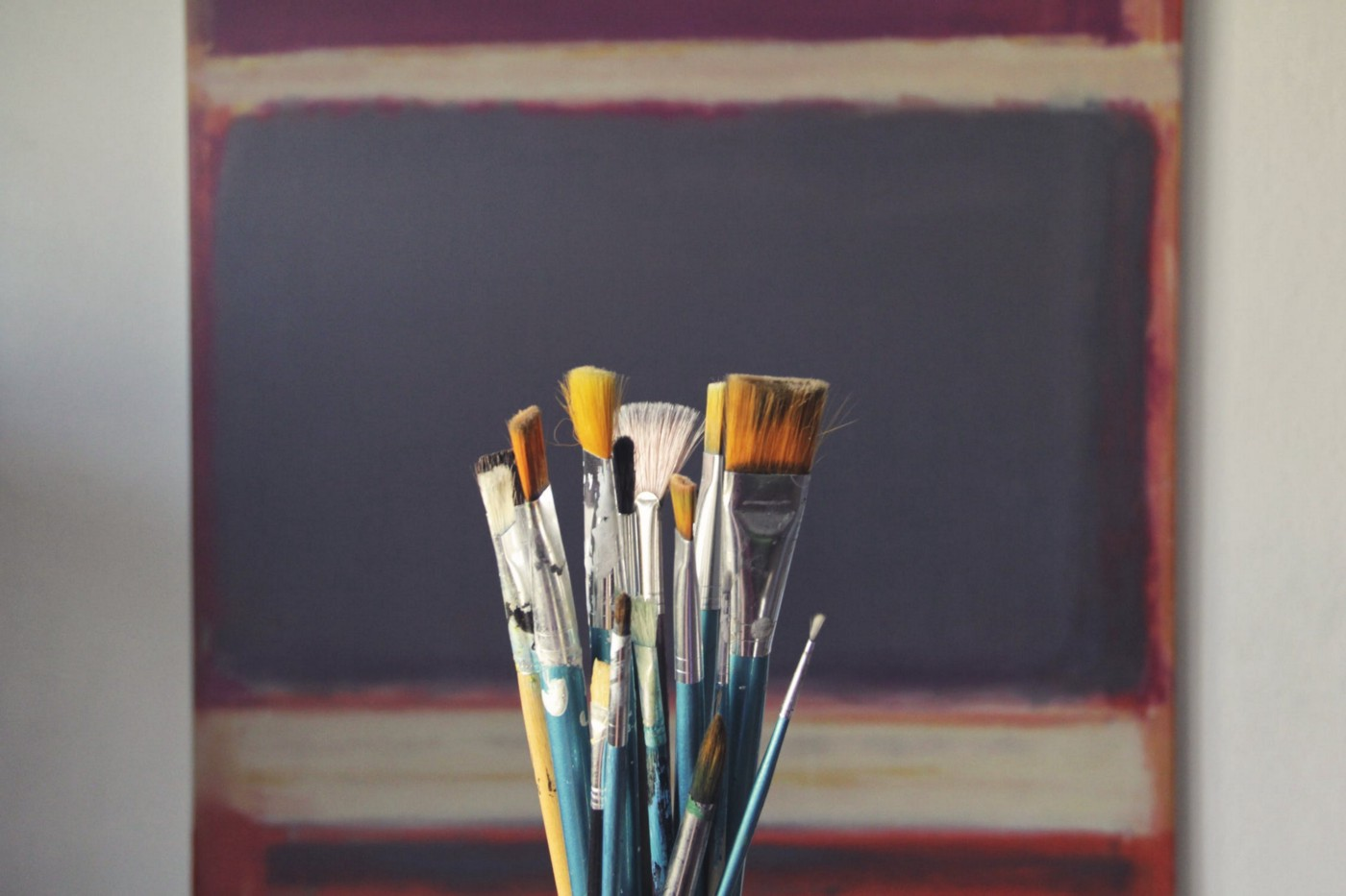 Paintbrushes in a jar in front of an abstract painting.