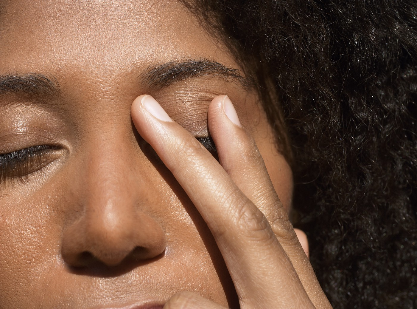 Young Black woman touching her eyelid in stress.