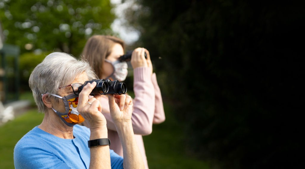Two women wearing face masks use binoculars to look in the distance.