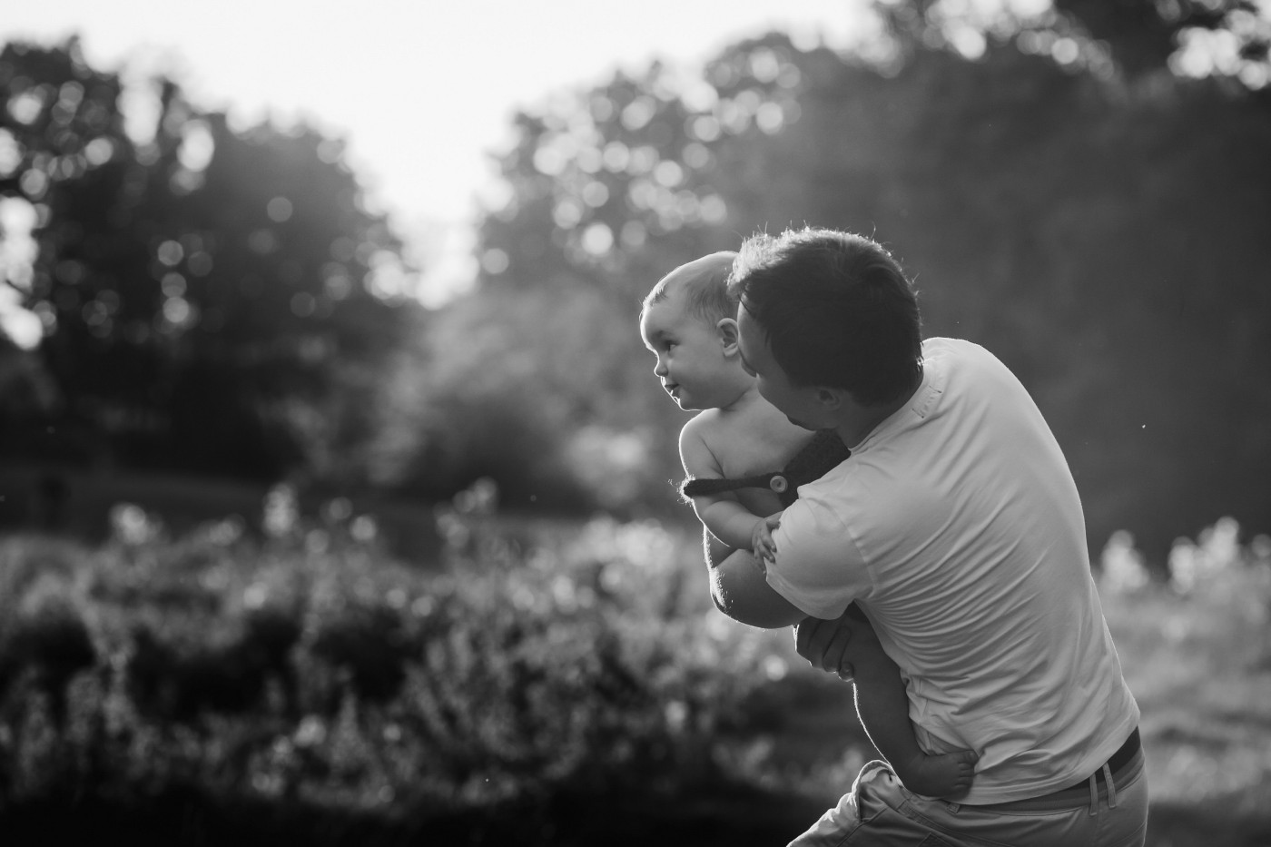 Toddler looking over father's shoulder, black and white