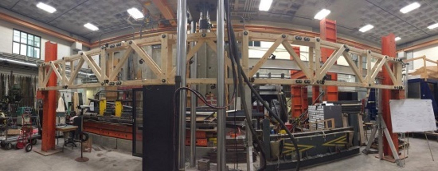 A wooden truss in a laboratory surrounded by testing equipment.