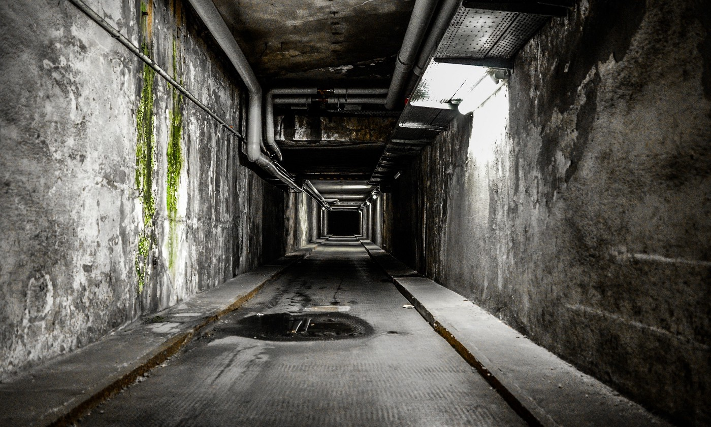 A long dark city alley underground, walls in decay on either side, a puddle in the foreground.