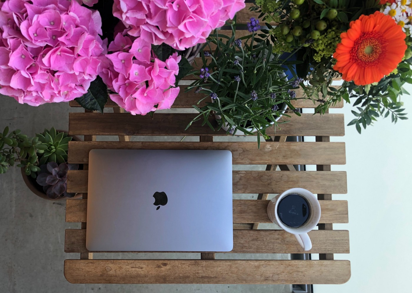 iPad, flowers, and a cup of coffee on a bench