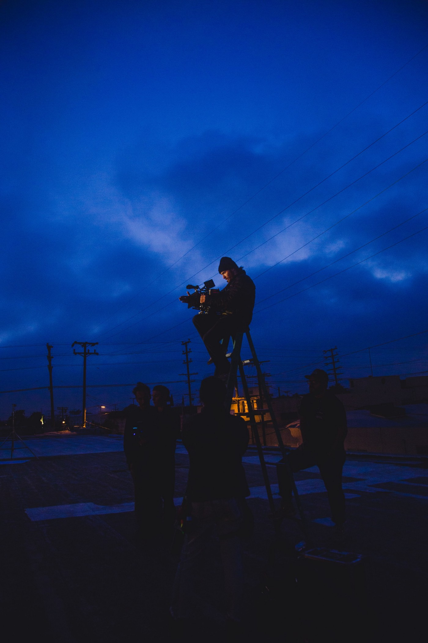 A camera operator sits on a stepladder against a blue night sky