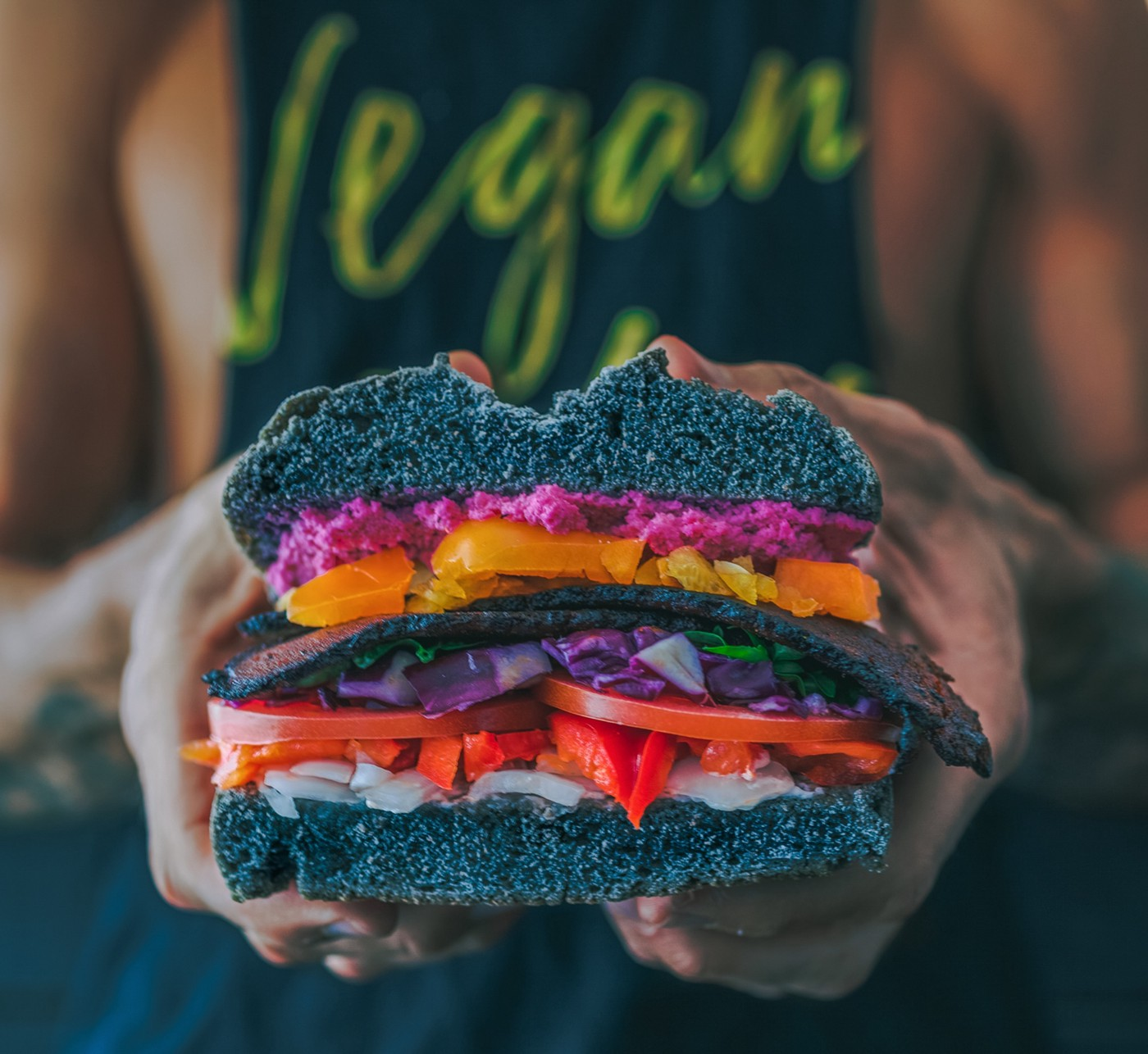 A sandwich with somewearing a t-shirt with the word vegan on it in the background.