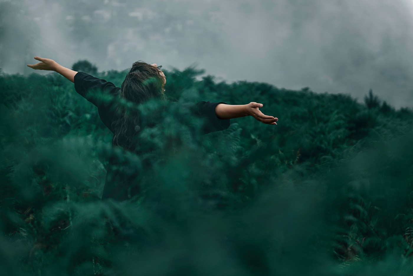 Woman standing in a field of dark green, only patialy visible, her arms open.