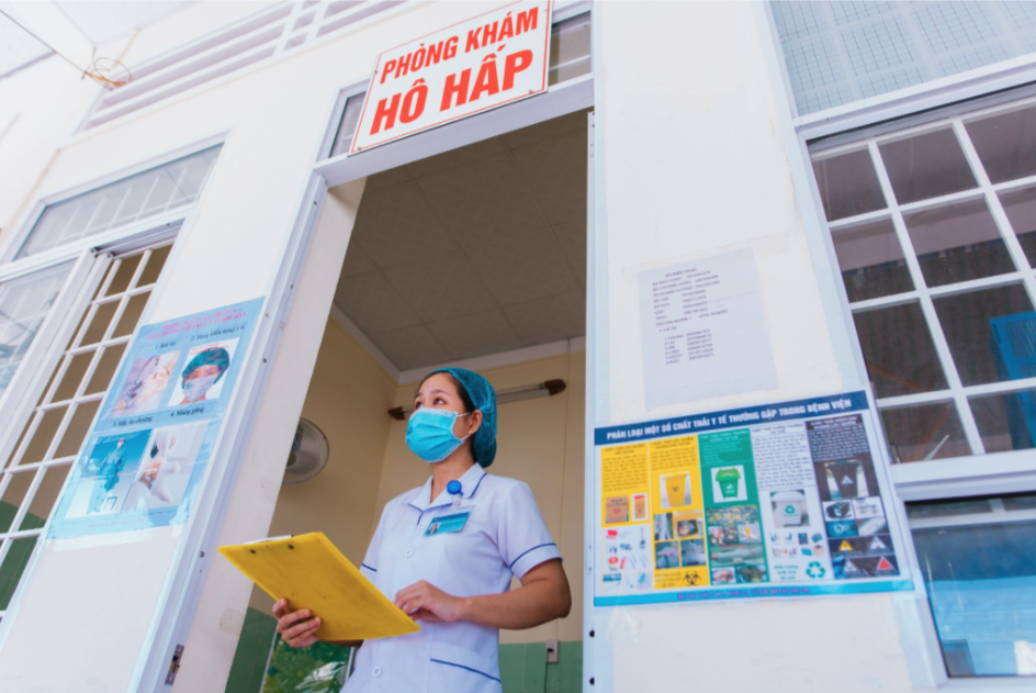 A healthcare worker stands outside a clinic in Vietnam.