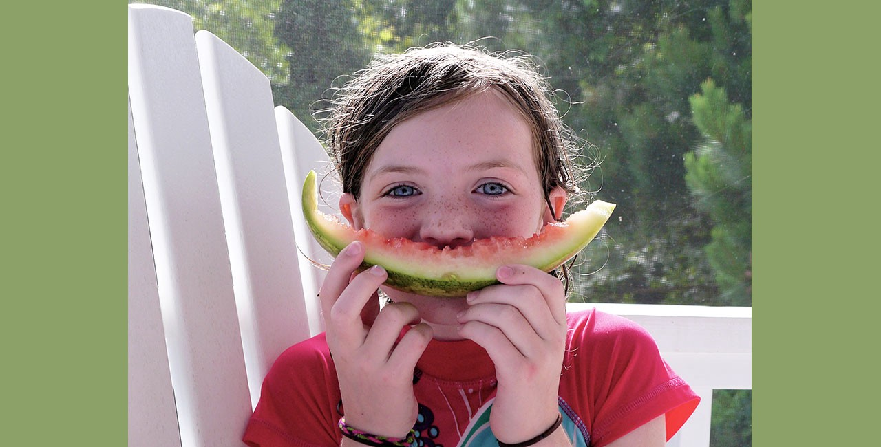 A little girl with blue eyes sitting in an Adirondack chair on a screened porch, holding an upcurved watermelon rind in front of her mouth