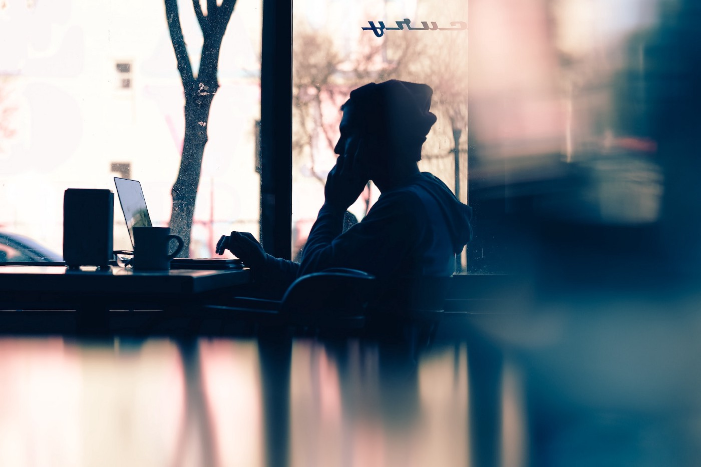 Person sitting at a desk with a laptop looking pensive.