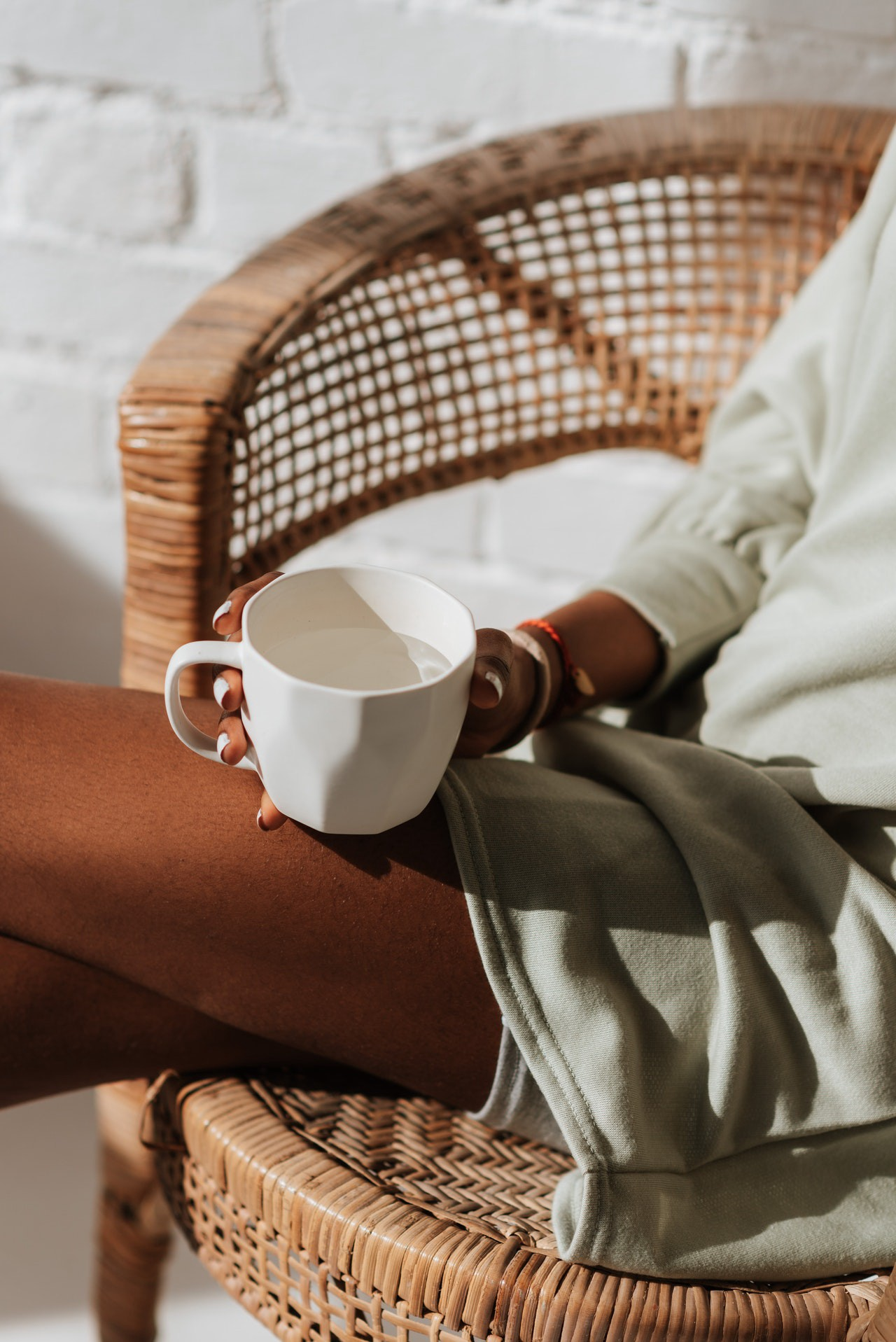 Black woman sitting quietly in a chair by herself holding a cup of water