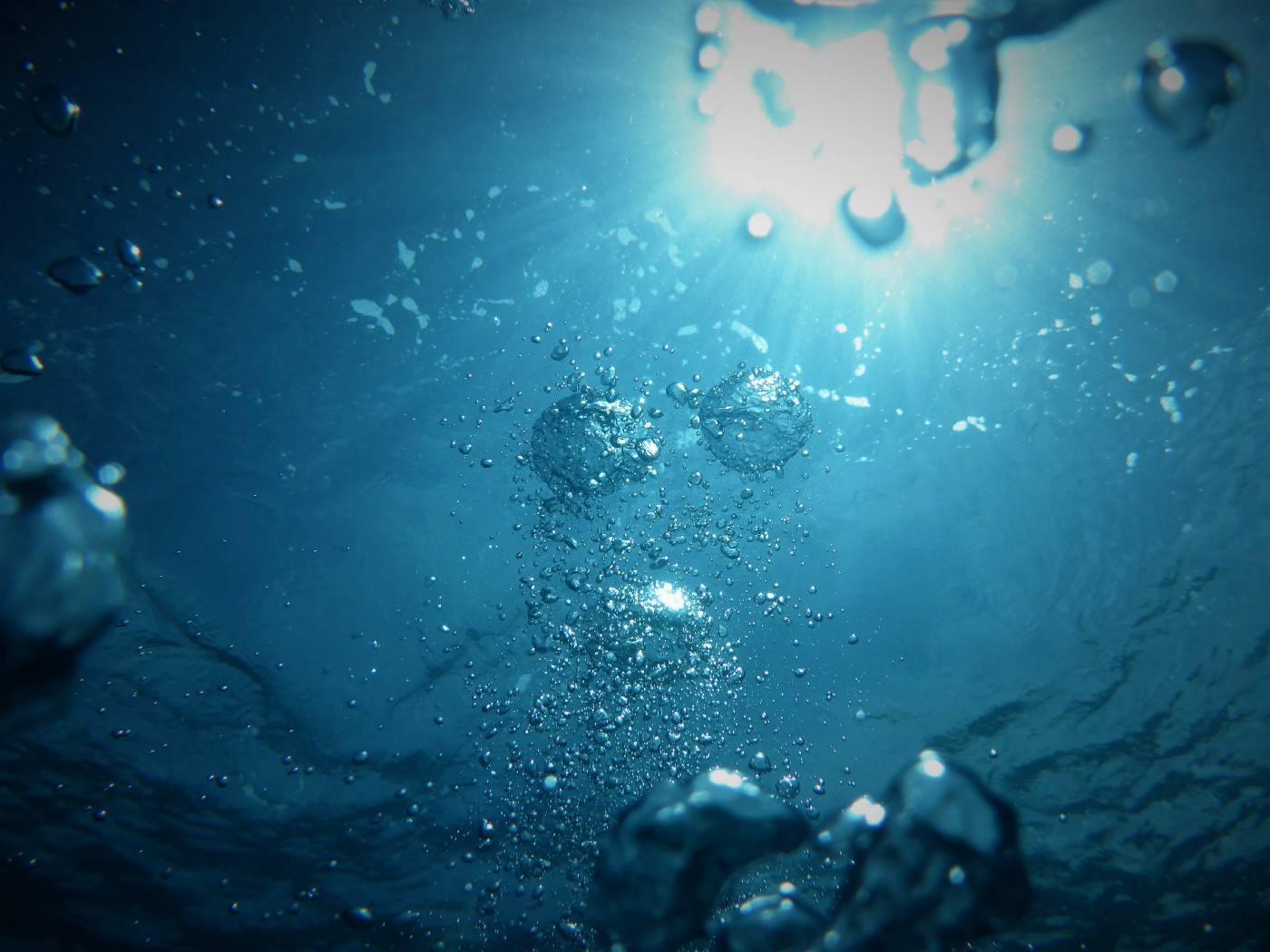 air bubbles rising to the surface of bright blue water with the sun shining through