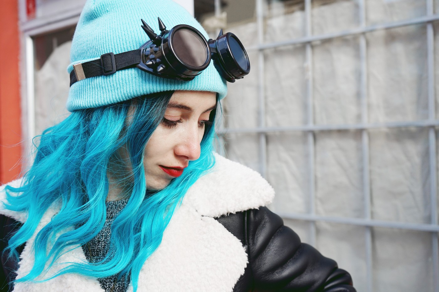 Woman with long electric blue hair in a black leather jacket and cyberpunk spike goggles over a blue beanie looking away from the camera