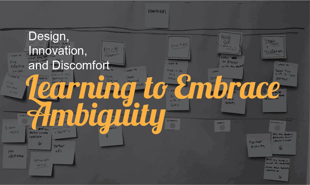 """The article title """"Learning to Embrace Ambiguity"""" written in yellow on top of a darkened picture of post-it notes."""