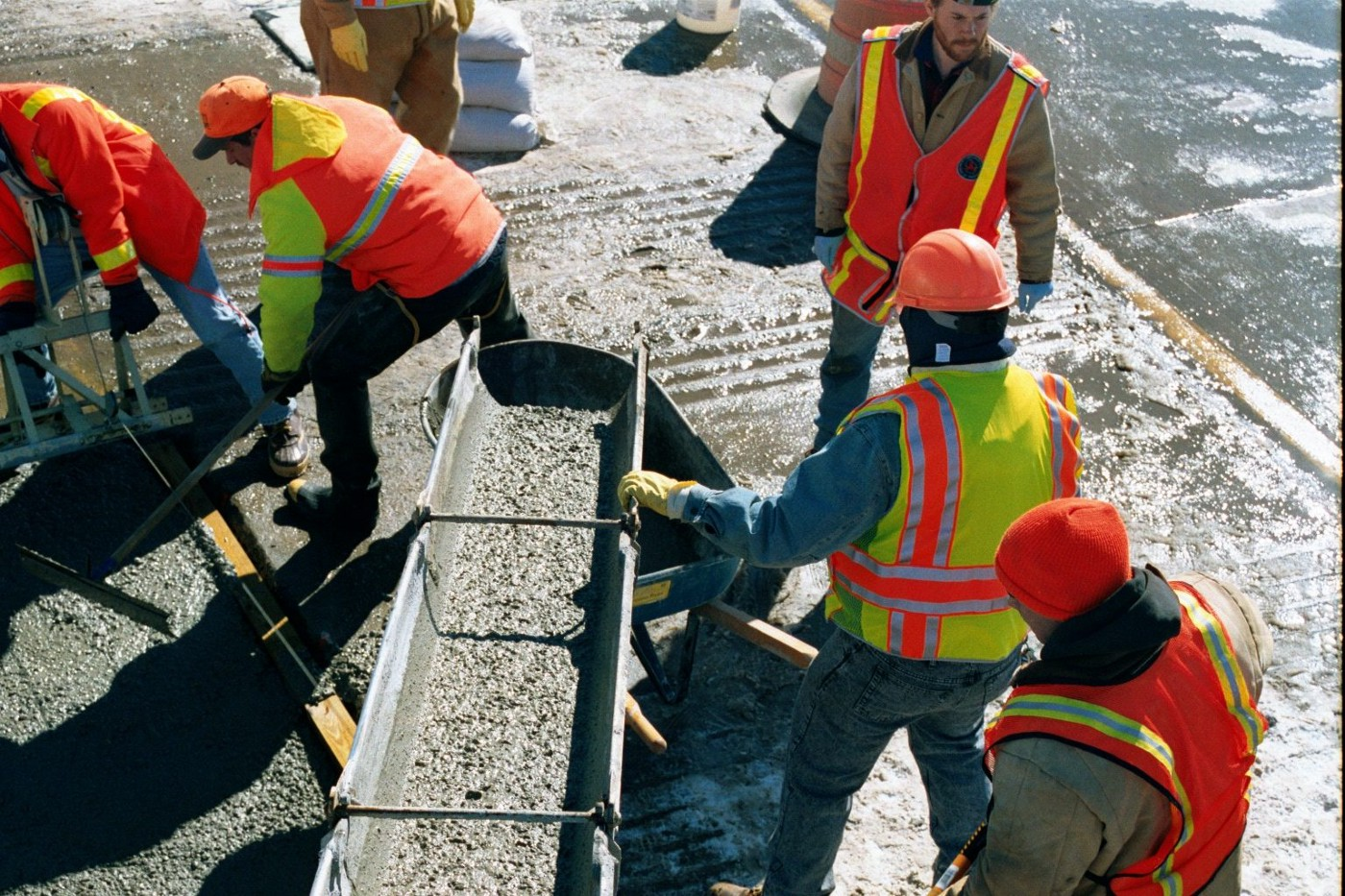 Several construction workers in hard hats and safety vests are pouring concrete at a worksite.