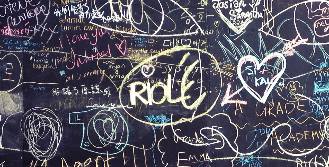 A blackboard covered with overlapping gaffiti in various colors of chalk