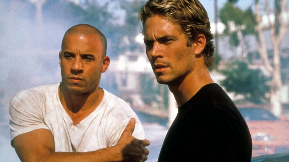 "A still from the 2001 film ""The Fast and the Furious"" featuring Vin Diesel on the left and Paul Walker on the right, both looking off to the left of the viewer."