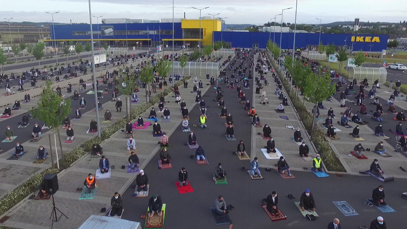 Muslim worshippers sitting at an Ikea car park