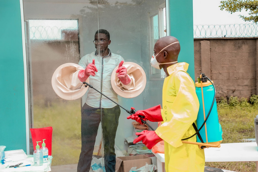 A health worker stands in a testing booth while another sanitizes his gloves.
