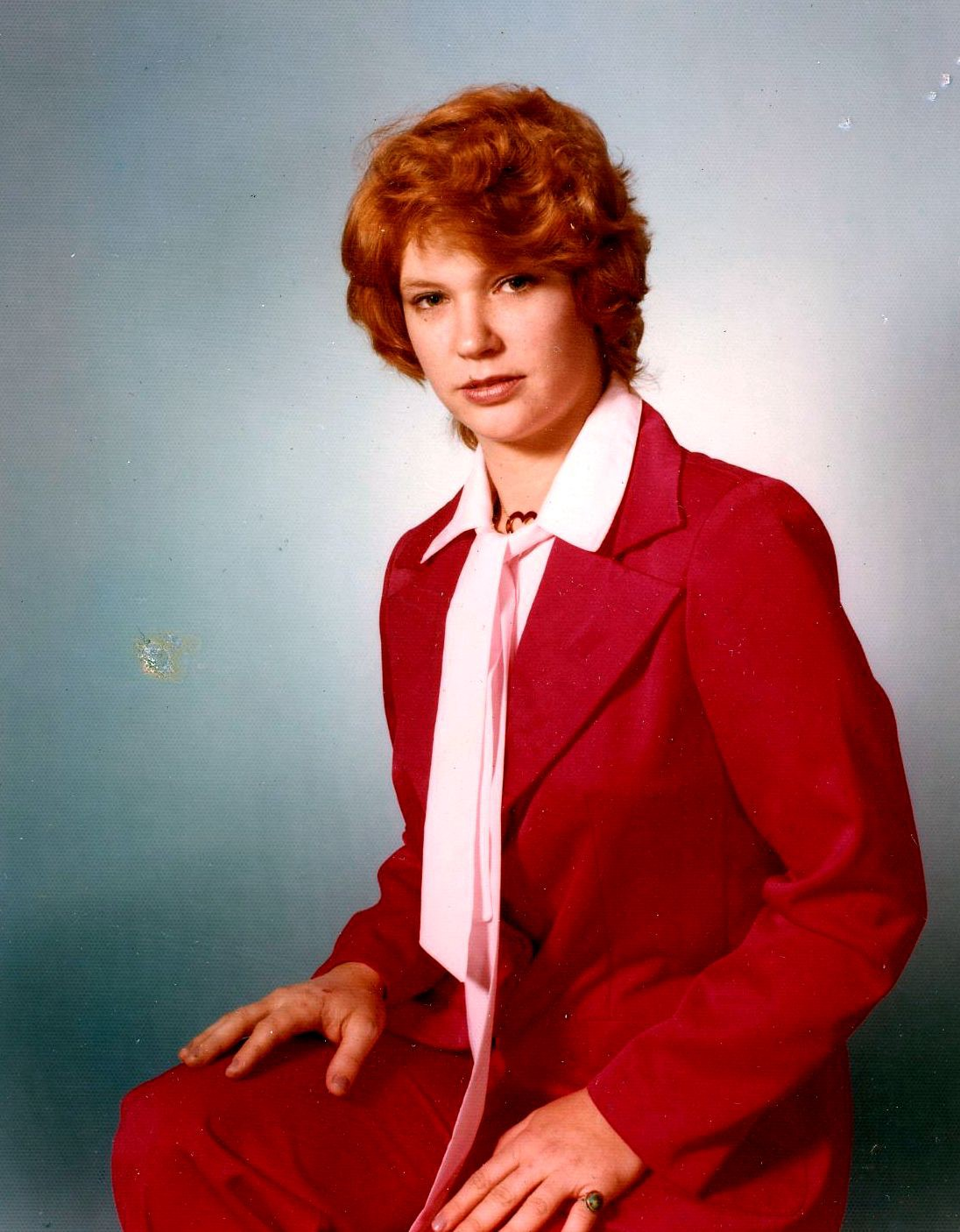 A young woman dressed in a red suit looks towards the camera.
