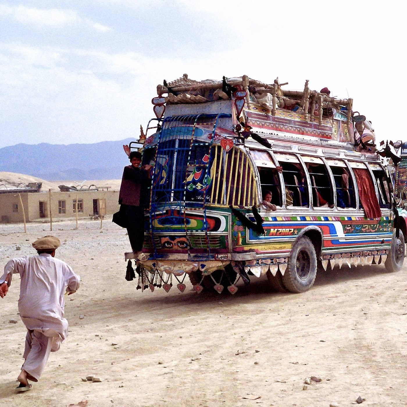 Man chasing a colorful bus in Afgh