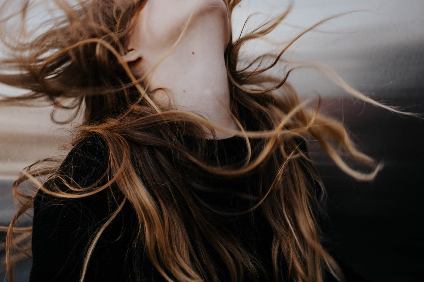 A ginger haired girl throwing her hair in the air in a powerful pose.