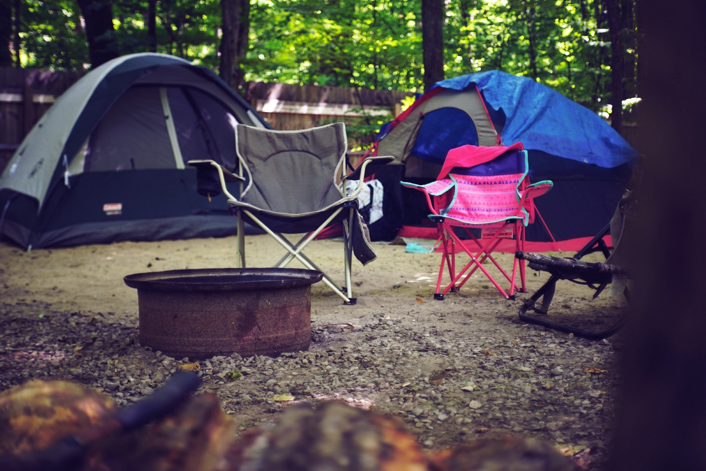 A camping ground set up with tents and chairs with a fire pit in the middle.