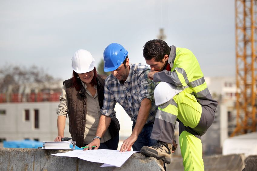 Three co-workers on a construction site figuring something out together.