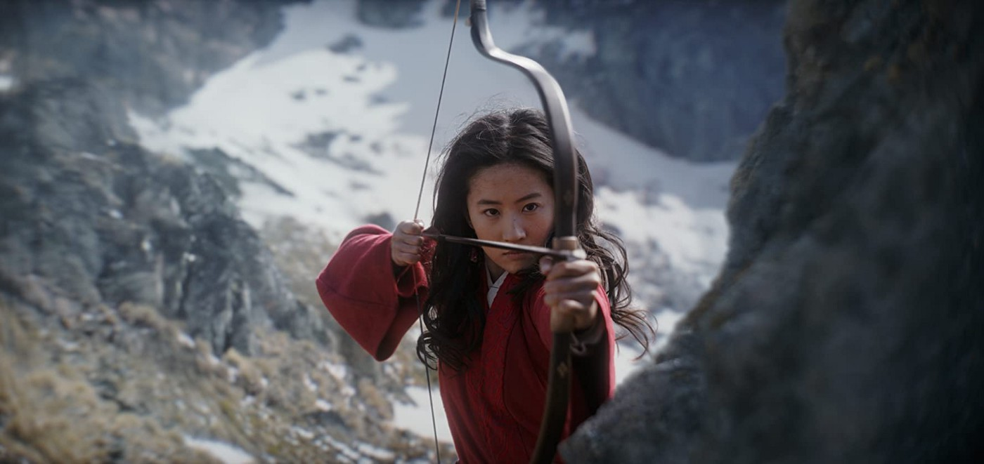 Mulan, from the live-action 2020 movie, is standing with her bow and arrow, ready to fire at the enemy.