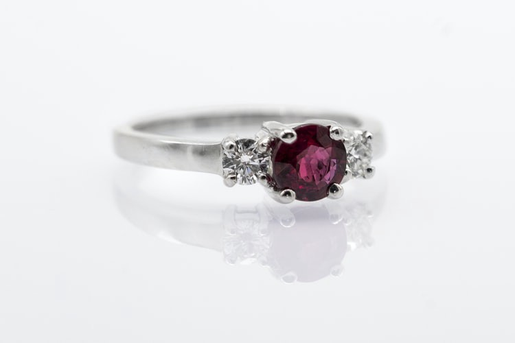 A ring with a purplish-red center stone.