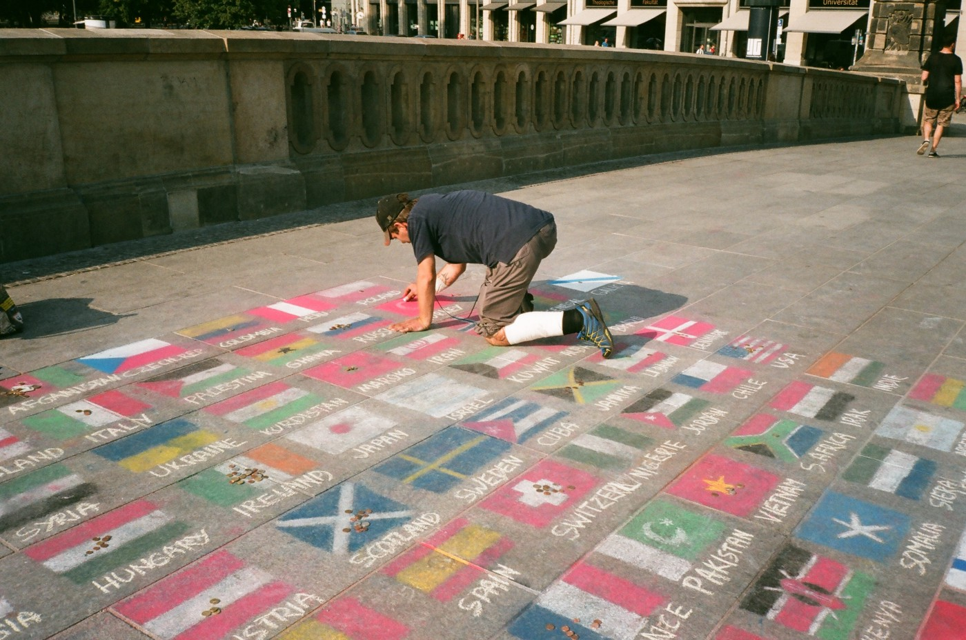 a man drawing flags of different countries with chalk on pavement