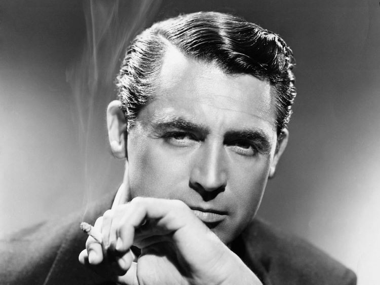 Classic film actor, Cary Grant poses with a cigarette in one hand. Smoke billows beside his face.