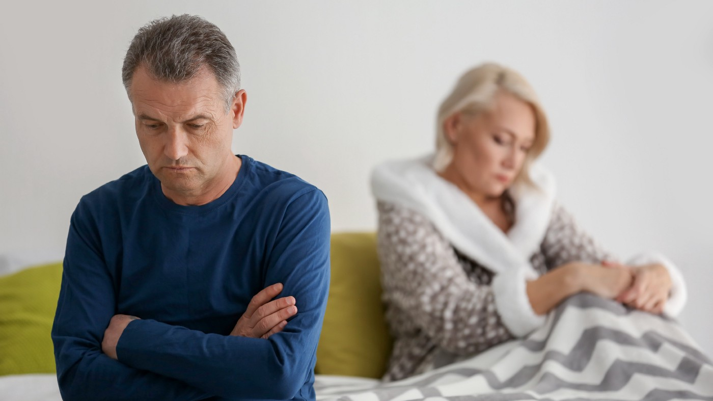 Older man who looks depressed and guilty, sitting on bed with his wife who looks withdrawn.