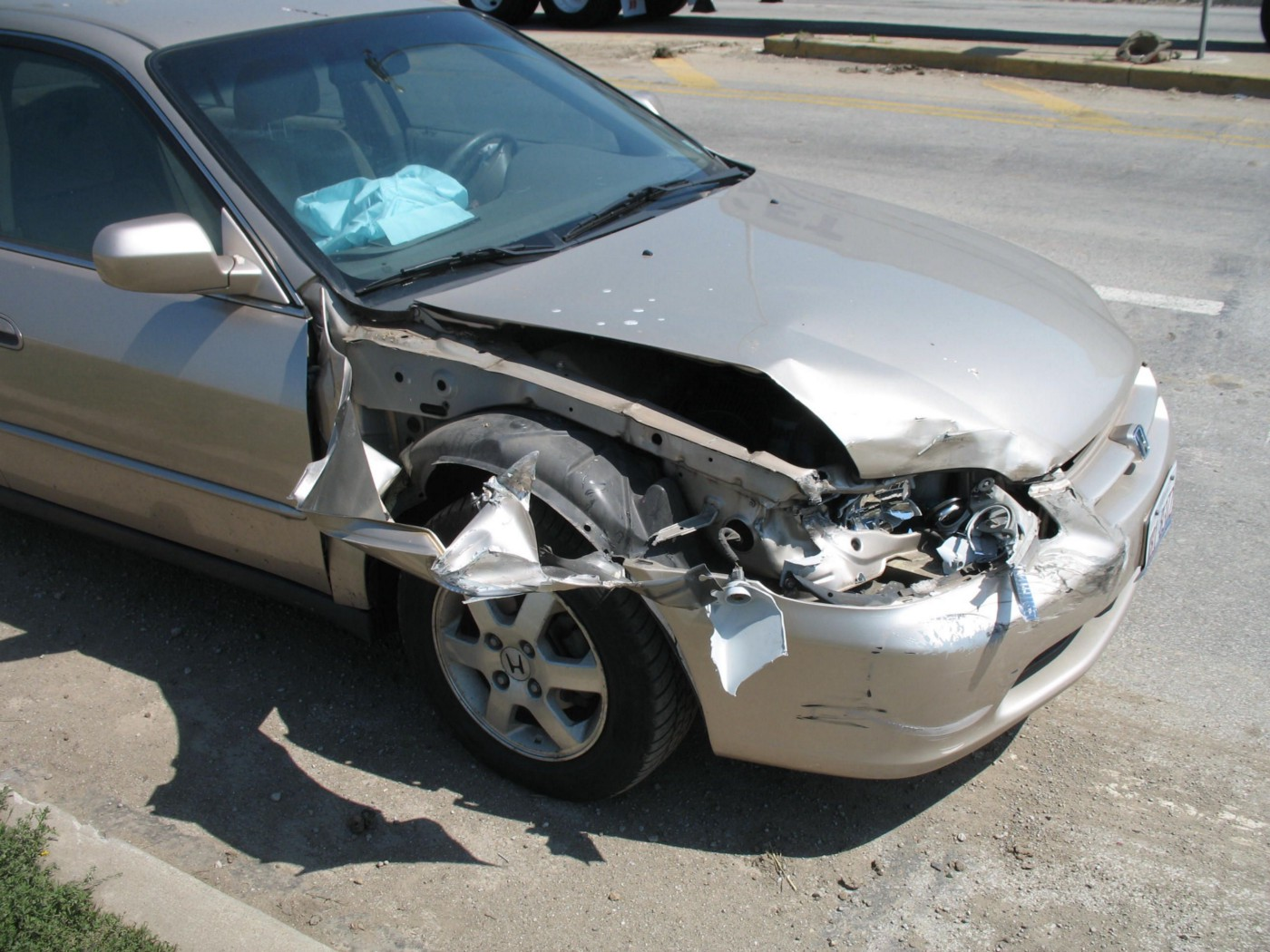 A smashed up, post-accident silver Honda Accord, airbags deployed.