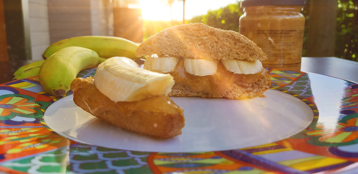 Two peanut butter and banana sandwiches on a plate, bananas, and a peanut butter jar. The sun is shining in the background.