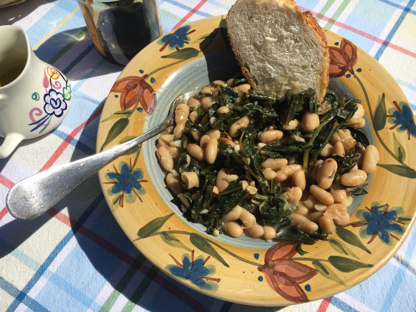 Dandelion greens and cannellini beans in a floral dish, served with a slice of crusty bread.