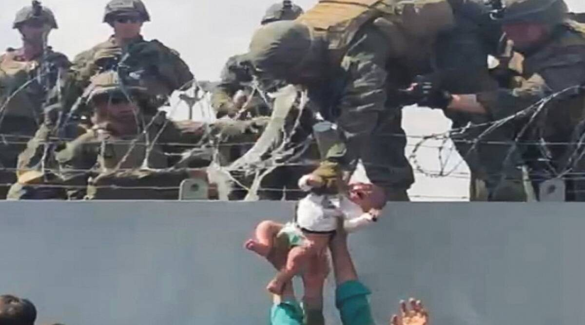 U.S. soldier reaches down to lift Afghan baby to safe area over a wall rimmed in barbed wire during hectic evacuation of Kabul.
