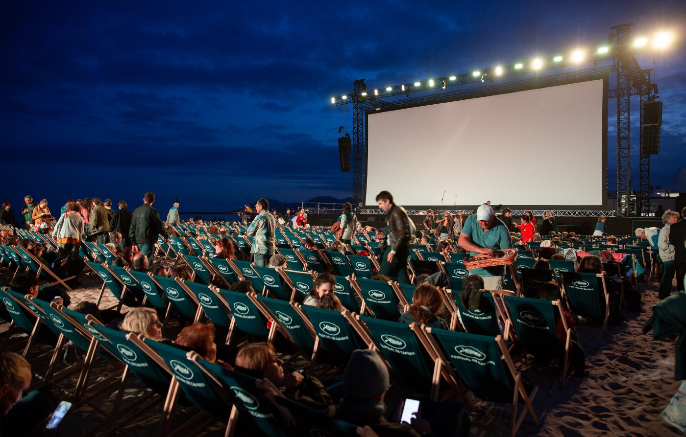 People sitting in seats in front of a large projector outdoors. The lights are on and some people are preparing stuff (moving around, buying food), while others have settled into their chairs and are awaiting the movie.