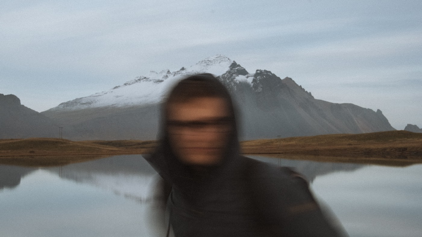 Blurred image of a man in a black hoodie standing in front of a lake and mountain.