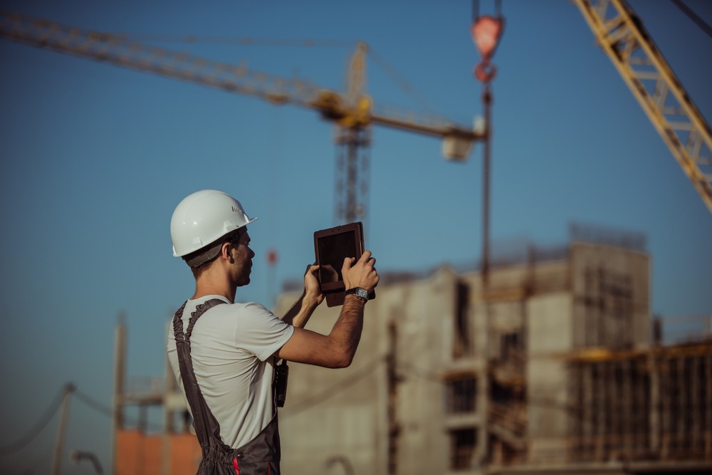 Worker taking a picture with an iPad on a construction site