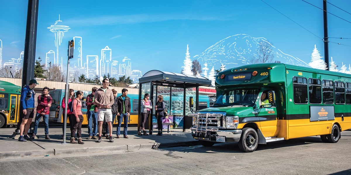 A small queue of people waits to board a King County Metro Trailhead Direct bus. A mountain and the Seattle skyline are digitally sketched in the background.