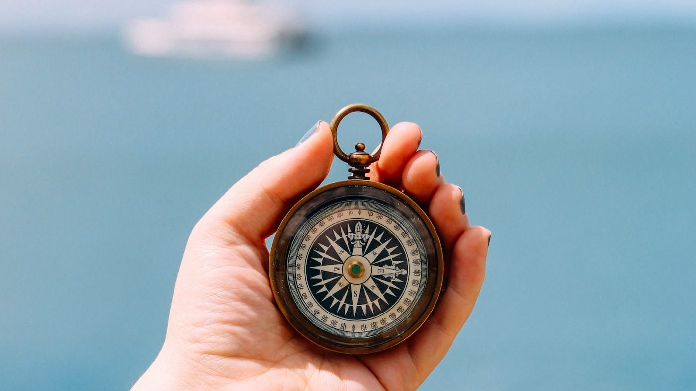 A hand holding up a nautical compass, in front of a large stretch of ocean. In the background is a ship.