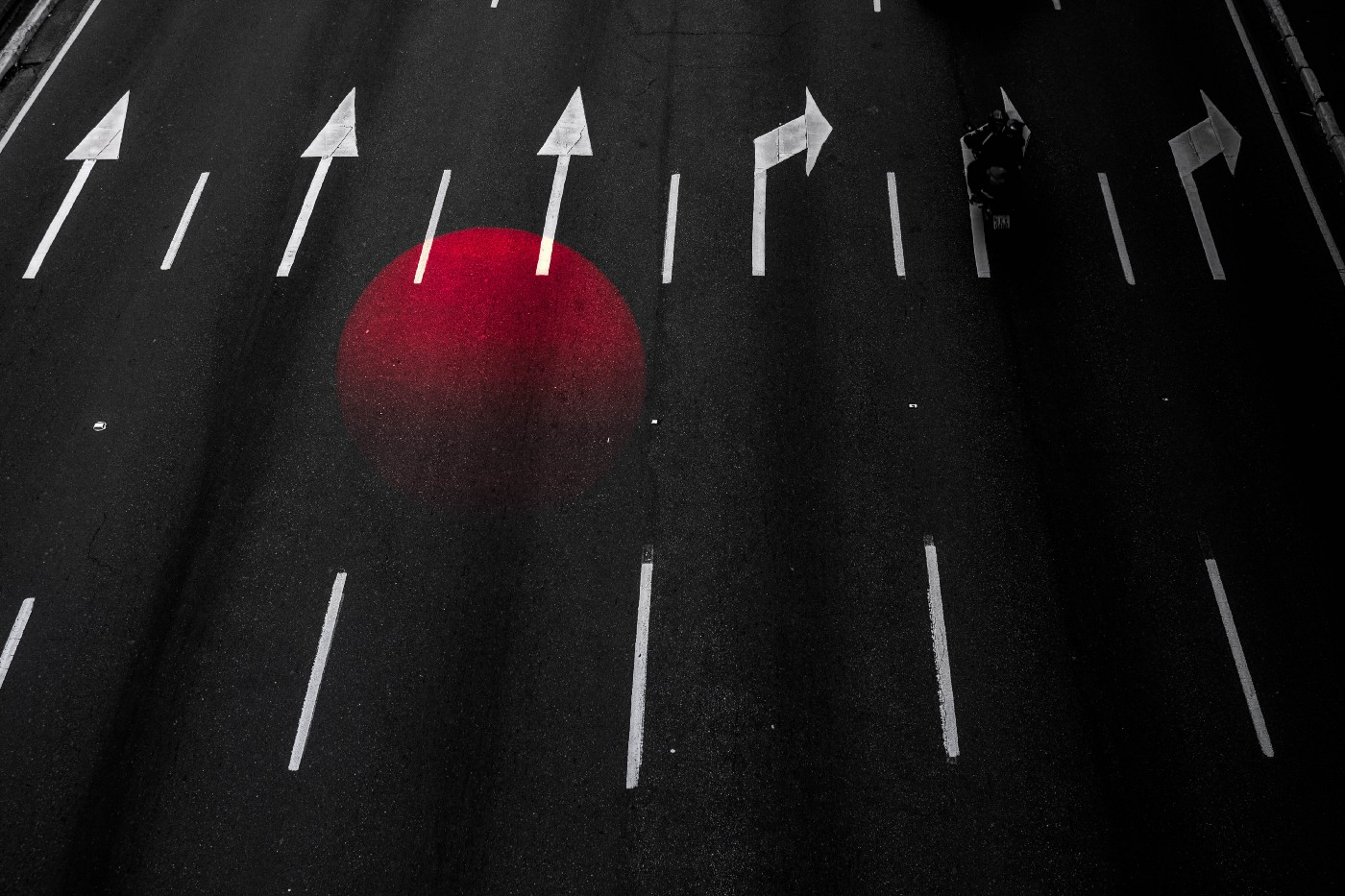 A roadway with some lanes marked with arrows pointing straight, others marking a turn, and a superimposed image of a red orb